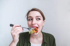 Retrato de uma menina bonita que coma uma salada com uma forquilha em um fundo cinzento Uma mulher bonita come uma refeição saudá fotos de stock royalty free