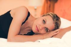 Retrato de uma menina bonita que encontra-se na cama Foto de Stock