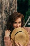 Retrato de uma menina bonita que esteja perto de uma árvore verão, caminhada na natureza, menina ruivo em um vestido do vintage e foto de stock