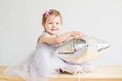 Retrato de uma menina bonita que joga com a prata estrela-dada forma Fotos de Stock