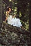 Retrato de uma menina bonita que levanta em uma rocha imagem de stock