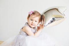 Retrato de uma menina bonita que veste o vestido cinzento elegante Foto de Stock Royalty Free