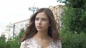 Retrato de uma menina bonita triste O cabelo longo desenvolve um vento no fundo da cidade filme