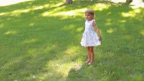 Retrato de uma menina bonito de cinco anos em um parque do verão na grama verde video estoque
