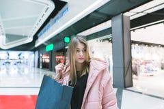 Retrato de uma menina bonito com compra nas mãos de um shopping moderno, bonito Conceito da compra Olhe afastado foto de stock