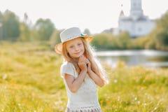 Retrato de uma menina bonito em um chapéu em um fundo de uma igreja em um dia de verão Fotos de Stock