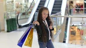 Retrato de uma menina bonito em um shopping com pacote com polegar acima video estoque