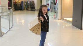 Retrato de uma menina bonito em um shopping com pacotes perto da escada rolante vídeos de arquivo
