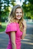 Retrato de uma menina bonito nova de sorriso bonita em um vestido cor-de-rosa do verão Imagem de Stock Royalty Free