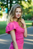 Retrato de uma menina bonito nova de sorriso bonita em um vestido cor-de-rosa do verão Imagem de Stock