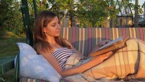 Retrato de uma menina bonito que lê um livro, encontrando-se sob uma cobertura no balanço filme