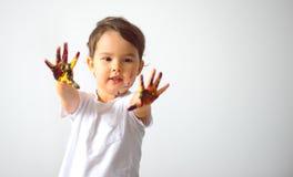 Retrato de uma menina bonito que mostra suas mãos pintadas em cores brilhantes isoladas Foto de Stock Royalty Free
