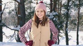 Retrato de uma menina bonito de sorriso em uma camisa e em um chapéu vermelhos, no sol da floresta do inverno video estoque