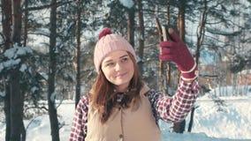 Retrato de uma menina bonito de sorriso que faz o selfie em uma camisa e em um chapéu vermelhos, no sol da floresta do inverno vídeos de arquivo