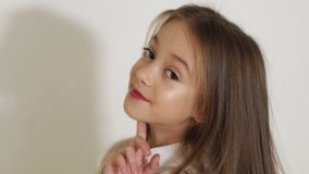 Retrato de uma menina de cabelos compridos pequena bonito no estúdio, ela que levanta para a câmera video estoque