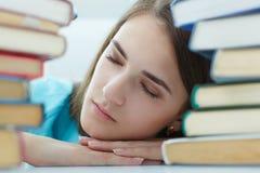 Retrato de uma menina cansado do estudante que dorme nos livros imagens de stock