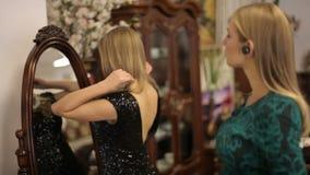 Retrato de uma menina com os fones de ouvido sem fio no primeiro plano Duas bonitas, meninas elegantes que estão perto do espelho filme