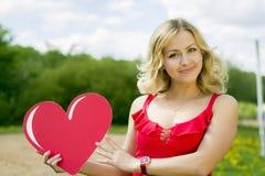 Retrato de uma menina com um coração em suas mãos Fotos de Stock Royalty Free