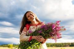 Retrato de uma menina com um grupo da salgueiro-erva em um campo verde Fotografia de Stock Royalty Free