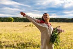 Retrato de uma menina com um grupo da salgueiro-erva em um campo verde Fotos de Stock Royalty Free