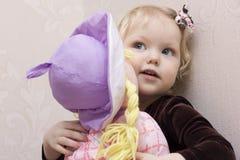 Retrato de uma menina com uma boneca. Imagens de Stock