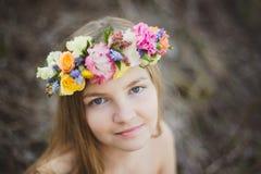 Retrato de uma menina com uma grinalda floral Fotos de Stock