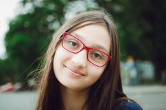 Retrato de uma menina consideravelmente adolescente com vidros Levantamento natural na rua imagens de stock royalty free