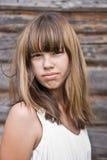 Retrato de uma menina de encontro a uma parede de madeira Imagem de Stock Royalty Free