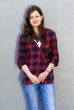 Retrato de uma menina de sorriso bonita na camisa e em vidros vermelhos sobre Imagens de Stock Royalty Free