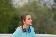 Retrato de uma menina desportiva com fones de ouvido azuis Fotos de Stock Royalty Free