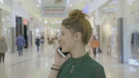 Retrato de uma menina do adolescente que ri e que inclina-se ao falar no telefone na alameda durante sua sessão da compra - video estoque