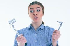 Retrato de uma menina duvidosa com uma ferramenta que não conheça o que fazer com ele, isolado no branco Imagens de Stock