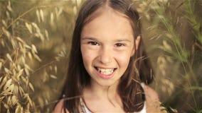 Retrato de uma menina em um campo da grama alta no por do sol filme