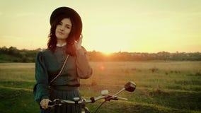 Retrato de uma menina em um chapéu em um vestido do vintage e com uma bicicleta no fundo do sol do por do sol filme