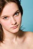 Retrato de uma menina em um fundo azul Imagens de Stock