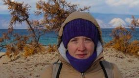 Retrato de uma menina em um revestimento com uma capa que está na costa do mar video estoque