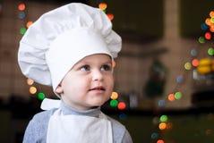 Retrato de uma menina em um tampão e em um cozinheiro chefe do avental Foto de Stock
