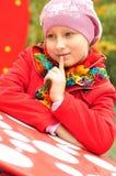 Retrato de uma menina em um tampão e em um revestimento Fotos de Stock Royalty Free