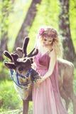 Retrato de uma menina em um vestido feericamente ao lado de uma rena Foto de Stock Royalty Free