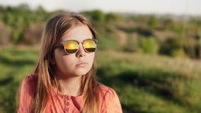 Retrato de uma menina em vidros de sol no por do sol vídeos de arquivo