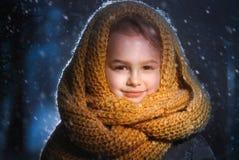 Retrato de uma menina encantador pequena em uma posição amarela do lenço de lãs exterior durante um blizzard da neve fotos de stock royalty free