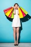 Retrato de uma menina entusiasmado feliz que guarda sacos de compras coloridos Foto de Stock Royalty Free
