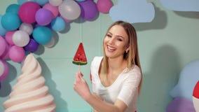 Retrato de uma menina feliz com uns doces grandes em um fundo de bolas multi-coloridas video estoque