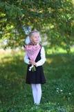Retrato de uma menina feliz da escola em um uniforme com o ramalhete das flores Imagens de Stock