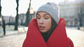Retrato de uma menina impressionante no chapéu cinzento e no revestimento vermelho que sorri quando estiver na rua antes das deco vídeos de arquivo