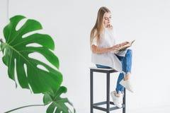 Retrato de uma menina loura à moda nova em um t-shirt branco e na calças de ganga que lê um livro em um fundo branco imagens de stock