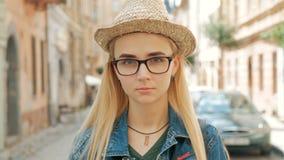 Retrato de uma menina loura bonita com vidros, um chapéu e um revestimento de calças de ganga video estoque
