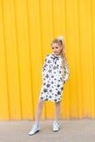 Retrato de uma menina loura bonita em um fundo amarelo Imagem de Stock