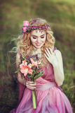 Retrato de uma menina loura bonita em um vestido cor-de-rosa com um ramalhete Fotos de Stock