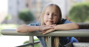 Retrato de uma menina loura bonita no balcão no verão filme